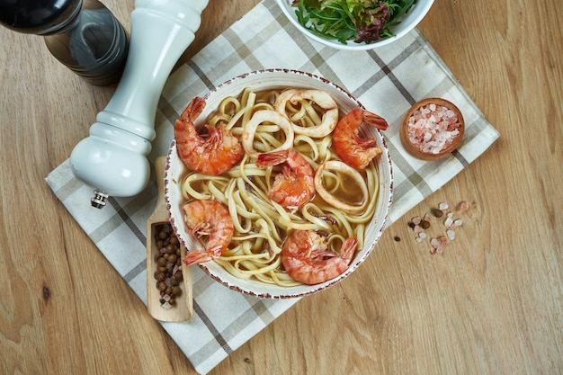 Sopa en el caldo con fideos y camarones, calamares en tazón de cerámica blanca sobre mesa de madera. sabrosa sopa de mariscos. comida plana
