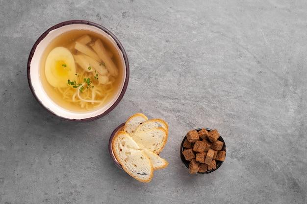 Sopa de caldo de pollo con huevo, fideos y pollo