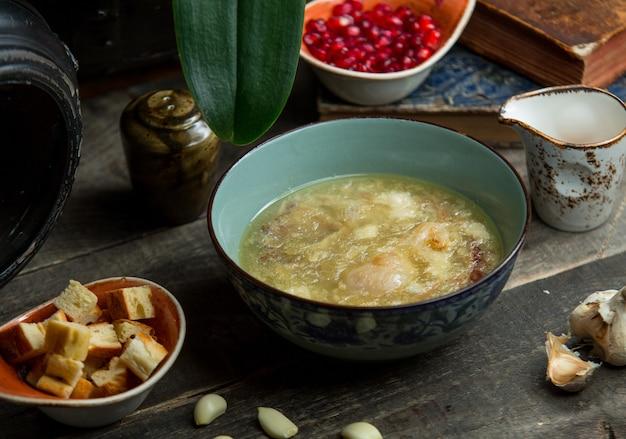 Sopa de caldo de pollo saludable servido con galletas de pan.