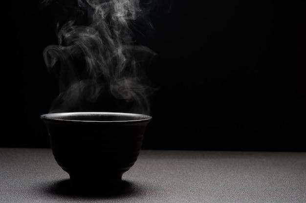 Sopa caliente en un tazón negro sobre mesa de madera, vapor de alimentos y espacio de copia, enfoque selectivo. concepto de alimentos frescos