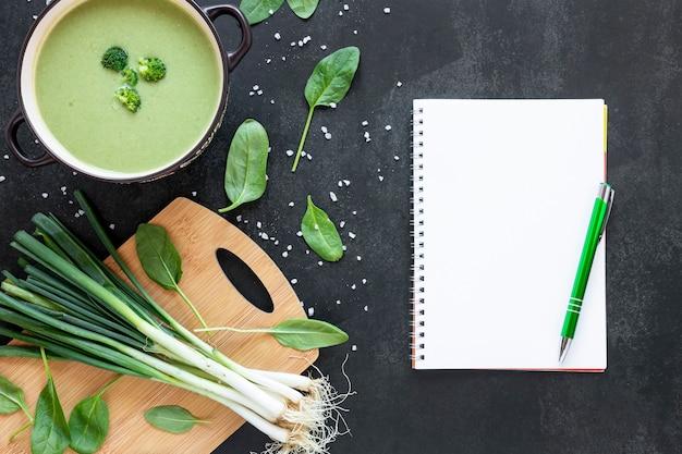 Sopa casera plana de brócoli y bloc de notas