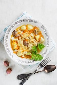 Sopa casera de pollo con fideos y papas con hojas de apio