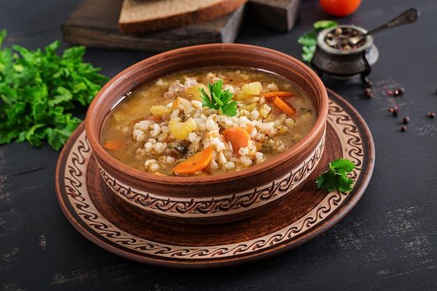 Sopa de cebada con zanahorias, tomate, apio y carne sobre una superficie oscura.