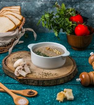 Sopa de champiñones con nueces sobre tabla de madera