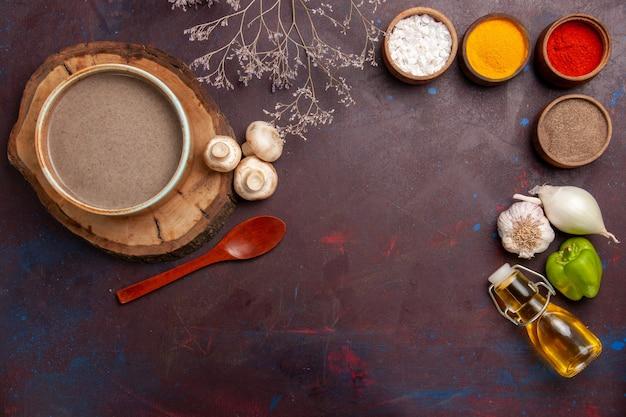 Sopa de champiñones de vista superior con diferentes condimentos en el espacio oscuro