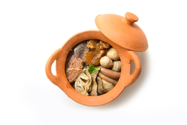Sopa clara de carne de res estofada (kaolao nuae toon) en la vista superior de la olla cray sobre fondo blanco
