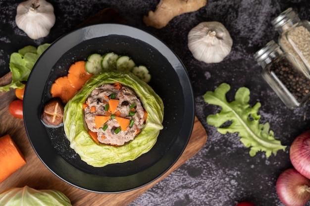 Sopa de col de cerdo con zanahorias, cebollas verdes picadas, pepino en una placa de madera sobre una placa de madera