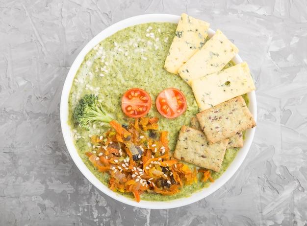 Sopa crema de brócoli verde con galletas en un tazón blanco, vista superior.
