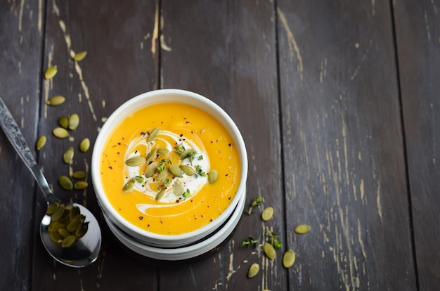 Sopa crema de calabaza con crema y semillas de calabaza en la vieja mesa rústica.