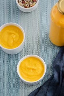 Sopa crema de calabaza con semillas en dos tazones blancos. vista superior.