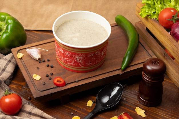 Sopa crema de champiñones en un tazón desechable servido con vegetales verdes.