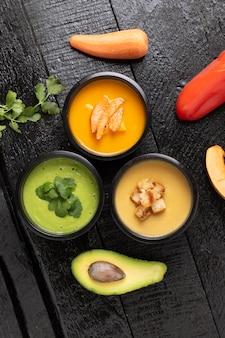 Sopa de crema de espinacas, sopa de calabaza y aguacate en recipientes de comida, plano. fondo de madera, vertical