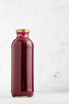 Sopa de crema de remolacha en botella de vidrio con fondo claro y espacio de copia.