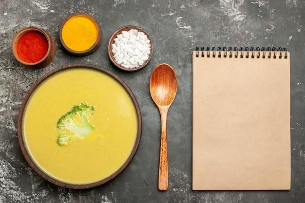 Sopa cremosa de brócoli en un cuenco marrón, cuchara de diferentes especias y cuaderno sobre mesa gris