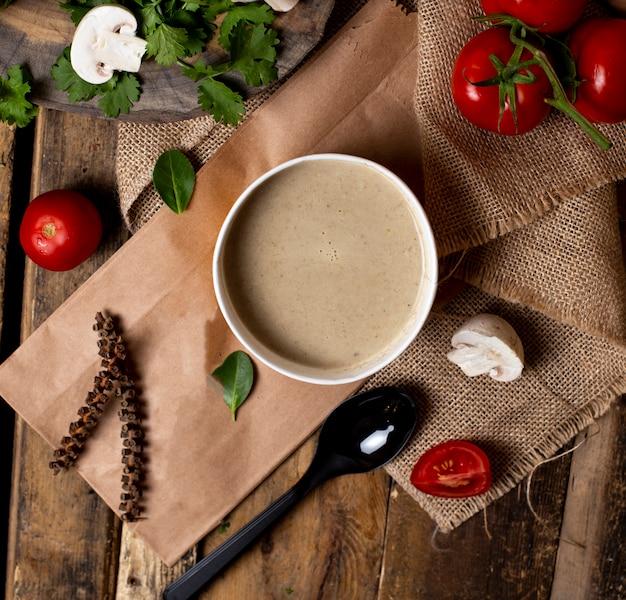 Sopa cremosa de champiñones en un tazón blanco con verduras