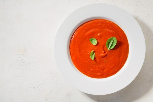 Sopa cremosa de tomate servida en un tazón