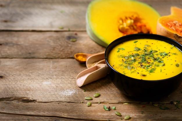Sopa cremosa de verduras y lentejas, calabaza cortada, semillas, perejil en madera rústica.