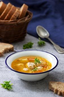 Sopa dietética con albóndigas, papas y fideos servidos con pan de centeno con salvado. menu de niños.
