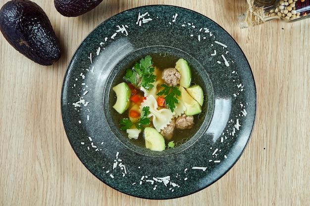 Sopa dietética con albóndigas de pavo, aguacate y pasta en la mesa de madera en un tazón negro. vista superior sabrosa sopa. comida plana