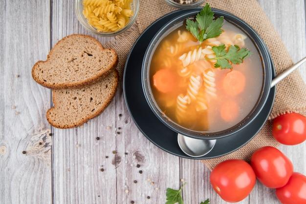 Sopa de diseño plano en un tazón con pan y tomates