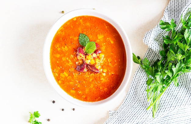 Sopa espesa casera de lentejas y frijoles rojos con verduras decoradas con hierbas.