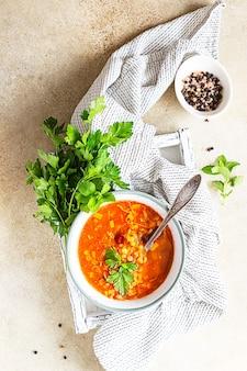 Sopa espesa de lentejas y frijoles rojos caliente y picante con tomates enlatados y cilantro.