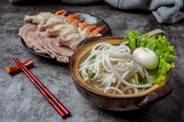 Sopa de estilo asiático con fideos, carne de cerdo y cebolla verde de cerca en un recipiente sobre la mesa.