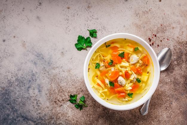 Sopa de fideos de pollo con perejil y verduras en un plato blanco, vista superior.