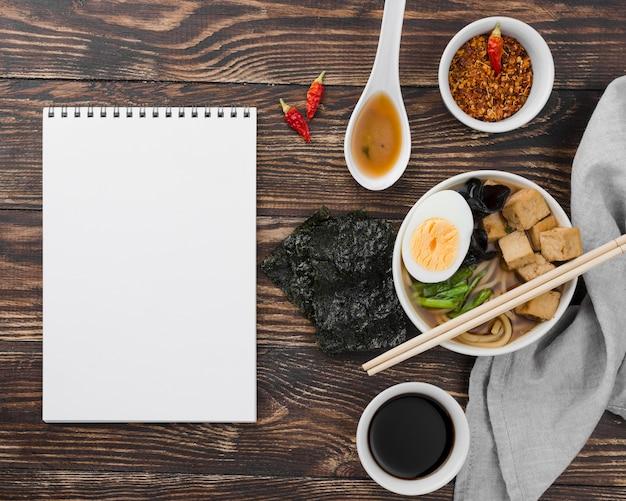 Sopa de fideos ramen asiáticos y bloc de notas