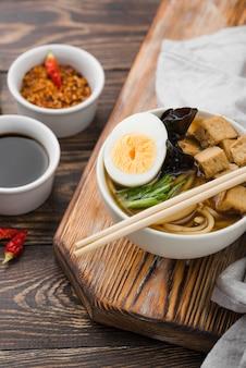 Sopa de fideos ramen asiáticos en tabla de cortar