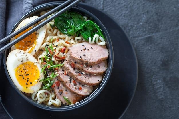 Sopa de fideos ramen japonesa con pechuga de pato, huevo, cebollino y espinacas