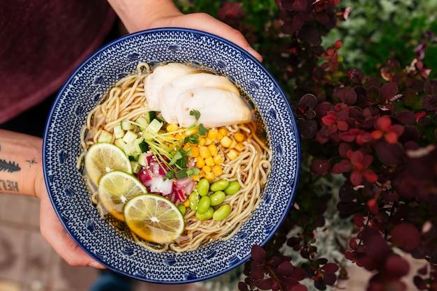 Sopa de fideos ramen de verano con pollo en las manos