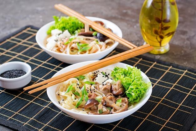 Sopa de fideos veganos con queso de soja, champiñones shiitake y lechuga en un tazón blanco. comida asiática.