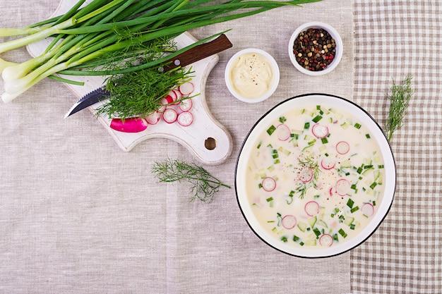 Sopa fría con pepinos frescos, rábanos, papas y salchichas con yogur en un tazón