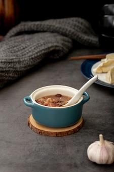 Sopa de frijoles en un frasco azul con ajo sobre un fondo gris