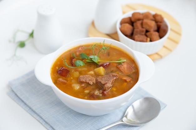 Sopa de guisantes con carne, salchicha ahumada, brotes de guisantes y picatostes.