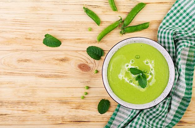 Sopa de guisantes verdes en un recipiente en la mesa de madera