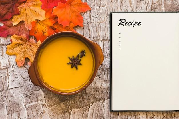 Sopa y hojas cerca del cuaderno con receta