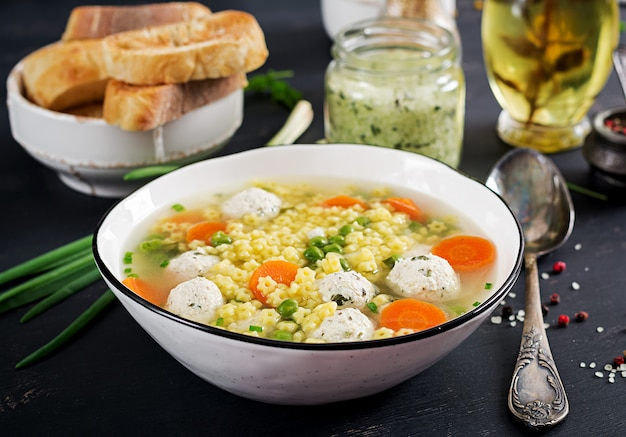 Sopa italiana de albóndigas y pasta sin gluten stelline en un tazón sobre la mesa negra. sopa dietética menú para bebés comida sabrosa.