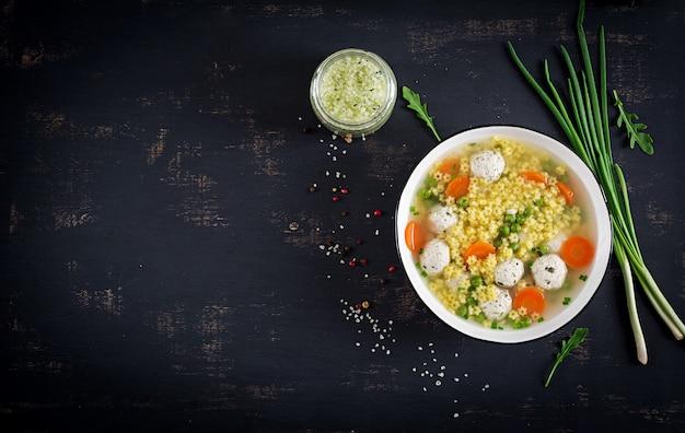 Sopa italiana de albóndigas y pasta sin gluten stelline en un tazón sobre la mesa negra.