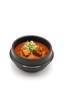 Sopa de kimchi aislado en el cuenco de piedra negra