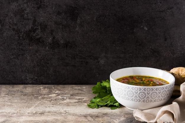 Sopa de lentejas indias dal (dhal) en un recipiente en la mesa de madera. copia espacio