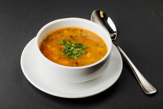 Sopa de lentejas con ingredientes mixtos y hierbas en un tazón blanco con una cuchara.