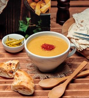 Sopa de lentejas con pan sobre la mesa 1