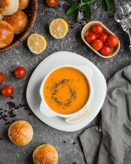 Sopa de lentejas con una rodaja de limón y una canasta con pan