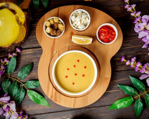 Sopa de lentejas con rodaja de limón y pan crujiente