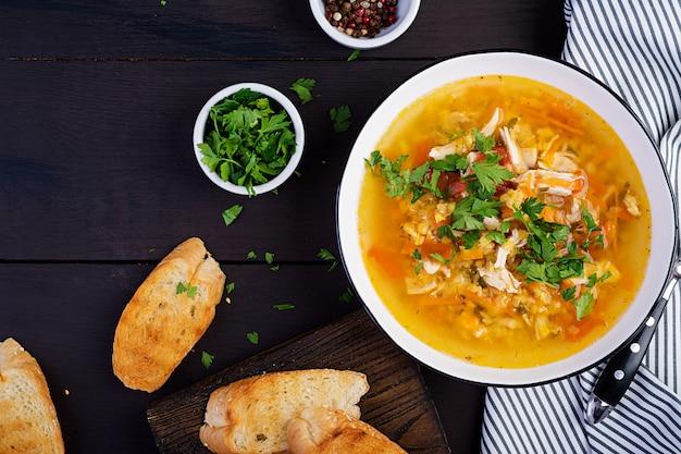 Sopa de lentejas rojas con carne de pollo y verduras.