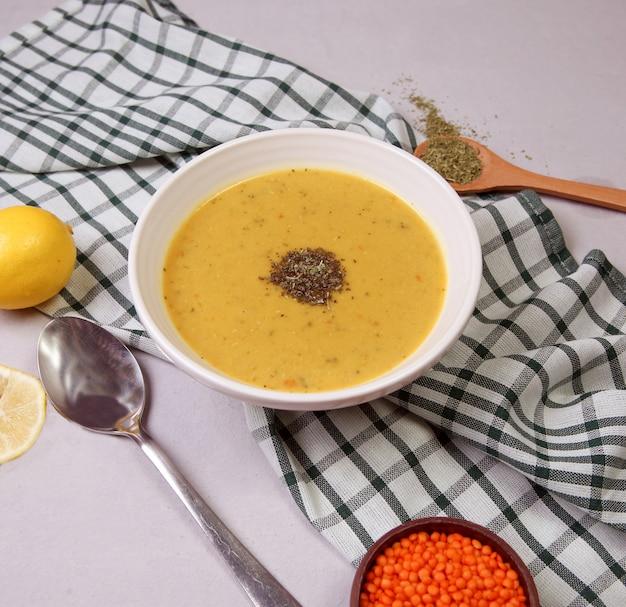 Sopa de lentejas rojas con hierbas en el tazón de fuente blanco.