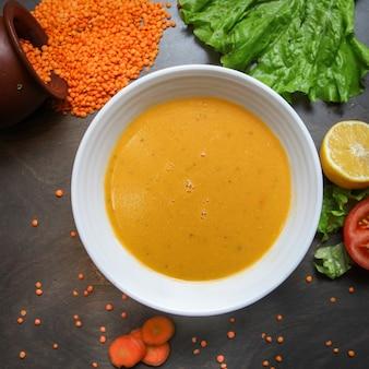 Sopa de lentejas rojas en un tazón con zanahoria, ensalada de hojas, limón, tomate, lentejas crudas
