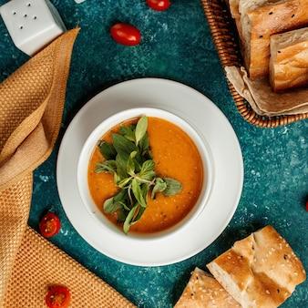 Sopa de lentejas en un tazón blanco y hierbas